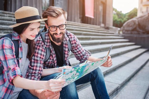 Молодой мужчина и женщина сидят на ступеньках снаружи. они держат карту вместе. туристы улыбаются. они смотрят на карту. путешественники отдыхают.