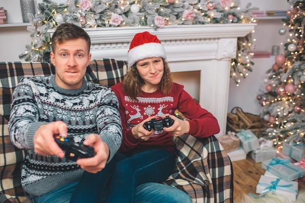 Молодой мужчина и женщина сидят и играют в игры вместе. они нажимают кнопки на консоли. люди волнуются.