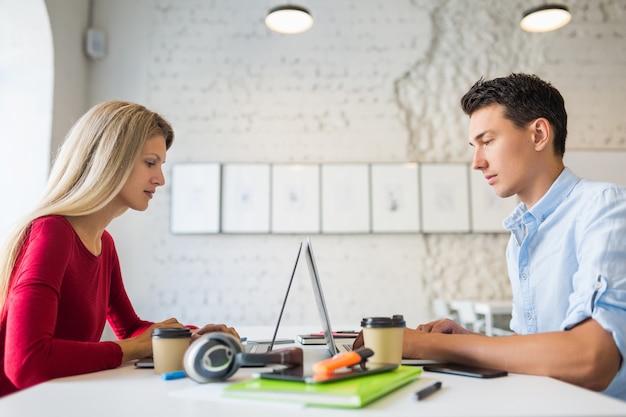 若い男と女が向かい合ってテーブルに座って、コワーキングオフィスのラップトップで働いて