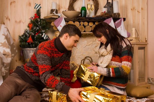 リボンと弓を熱心に解くエレガントなメタリックゴールドのクリスマスプレゼントを開く素朴な木製の小屋の床に座っている若い男性と女性