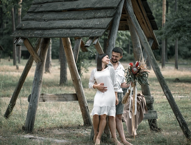 젊은 남자와 여자는 이국적인 꽃의 꽃다발, 결혼의 로맨스와 함께 숲에서 껴안고 세련되게 옷을 입고 있습니다.