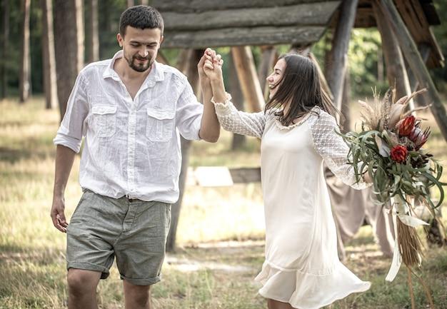 이국적인 꽃의 꽃다발과 함께 세련되게 차려입은 젊은 남녀가 자연 속에서 데이트를 하며 숲을 걷고 있습니다.
