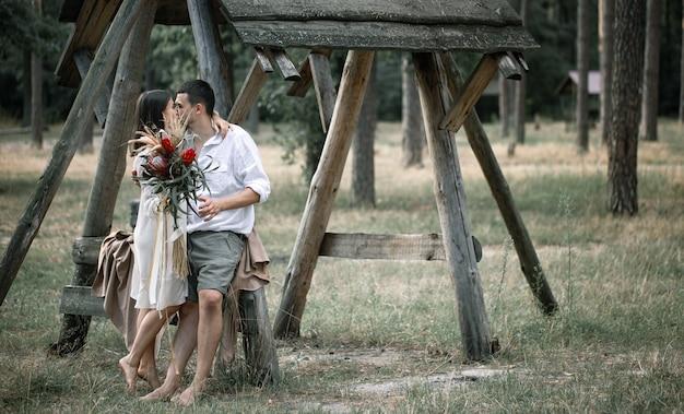 젊은 남자와 여자는 이국적인 꽃의 꽃다발과 함께 세련되게 옷을 입고, 숲에서 키스, 결혼에서의 로맨스의 개념.