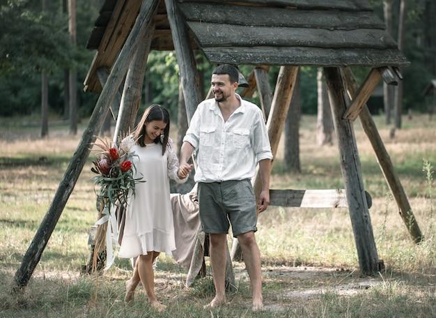 젊은 남자와 여자는 숲에서 데이트에 이국적인 꽃의 꽃다발과 함께 세련되게 차려입었습니다.