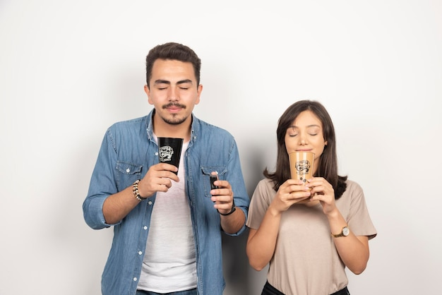 若い男性と女性がカップからアロマコーヒーを嗅ぎます。