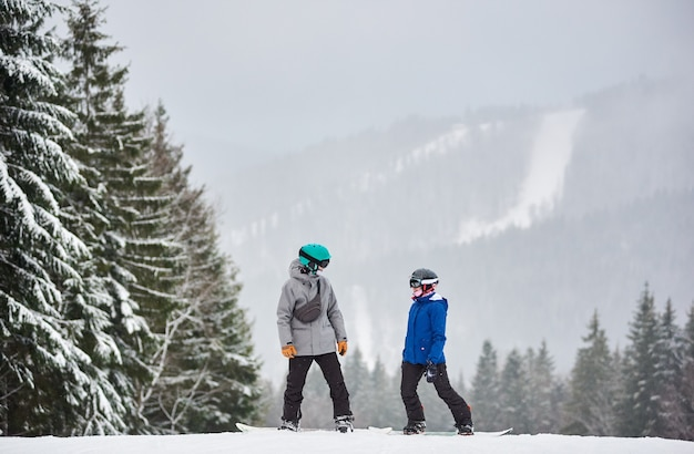 雪に覆われた高い斜面に立って、お互いを見つめている若い男性と女性のスノーボーダー。背景に降雪。