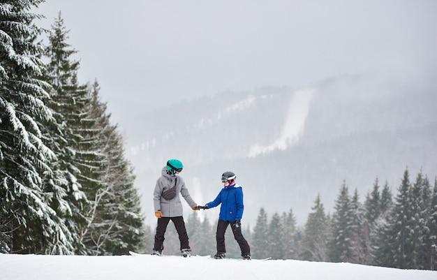Молодой мужчина и женщина сноубордист, стоя на высоком заснеженном склоне и глядя друг на друга. снегопад на фоне.