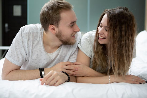 若い男性と女性、ベッドに横になって手をつないでお互いに話し合う楽しい何か
