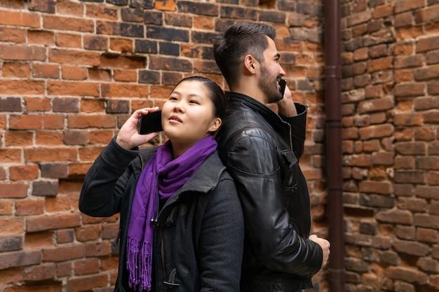 若い男性と女性は、携帯電話で話しているレンガの壁の近くに背中合わせに立っています