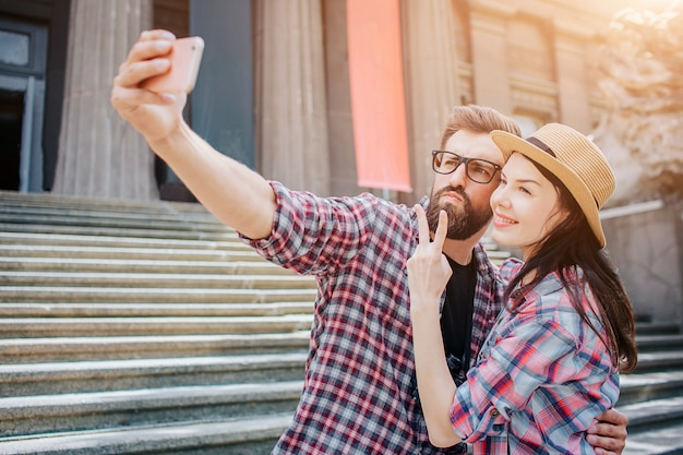 Молодой мужчина и женщина стоят вместе и принимает селфи. он держит камеру в руке. они ставят. люди стоят на лестнице.