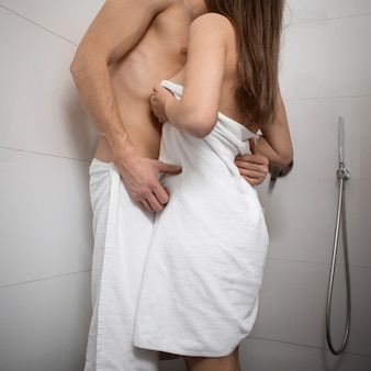 Молодой мужчина и женщина, стоя в белой ванной комнате и обнимая друг друга. сексуальная обнаженная пара любви. концепция дня святого валентина.