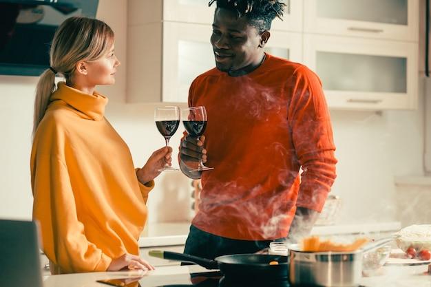 젊은 남자와 여자는 부엌에서 서로 반대편에 서서 신중하게 레드 와인으로 안경을 떨리는
