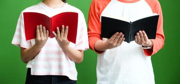 緑の壁の背景の前に立って、読書の若い男女の学生