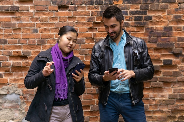 若い男性と女性は、レンガの壁の背景にスマートフォンを見ながら互いに話します