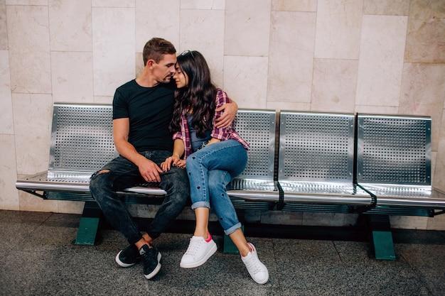 젊은 남자와 여자는 지하에서 사용합니다. 지하철에서 몇 가지. 벤치에 앉아