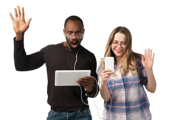 젊은 남자와여자가 흰색 스튜디오 배경에 고립 된 노트북, 장치, 가제트를 사용 하여.