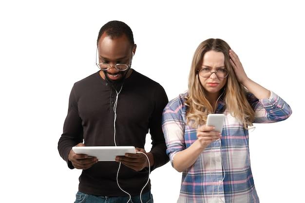 Молодой мужчина и женщина, используя ноутбук, устройства, гаджеты, изолированные на белой стене. концепция современных технологий, технологий, эмоций, рекламы. copyspace. покупки, игры, онлайн-обучение знакомств.