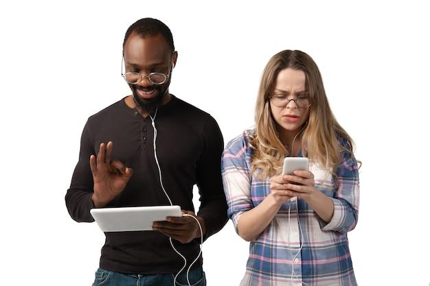 Молодой мужчина и женщина, используя ноутбук, устройства, гаджеты, изолированные на белой стене. концепция современных технологий, технологий, эмоций, рекламы. copyspace. шоппинг, игры, онлайн-обучение знакомств. Premium Фотографии