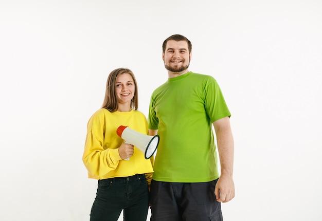 Молодой мужчина и женщина в цветах флага лгбт на белой стене. кавказские модели в ярких рубашках. выглядите счастливым, улыбающимся и обнимающимся. концепция гордости, прав человека и выбора лгбт. держа мундштук.