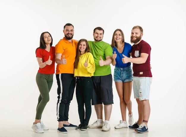 Молодой мужчина и женщина в цветах флага лгбт на белой стене. кавказские модели в ярких рубашках. выглядите счастливым, улыбающимся и обнимающимся. концепция гордости, прав человека и выбора лгбт.