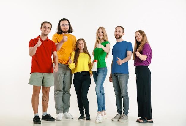 若い男性と女性は白い壁にlgbtの旗の色を着ています。明るいシャツを着た白人モデル。一緒に幸せそうに見え、笑顔で抱きしめます。 lgbtのプライド、人権、選択の概念。