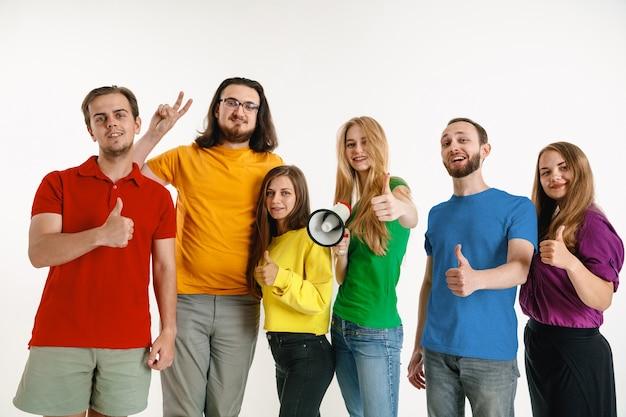 若い男性と女性は白い壁にlgbtの旗の色を着ています。明るいシャツを着た白人モデル。