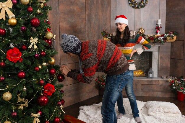 面白い帽子をかぶって、リビングルームの大きなクリスマスツリーに飾りをぶら下げてクリスマスを飾る若い男性と女性