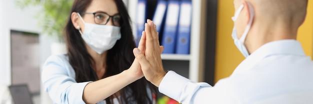 Молодой мужчина и женщина в защитных медицинских масках дают пять за столом в офисе