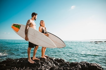 Young man and woman with surf boards on rock near sea