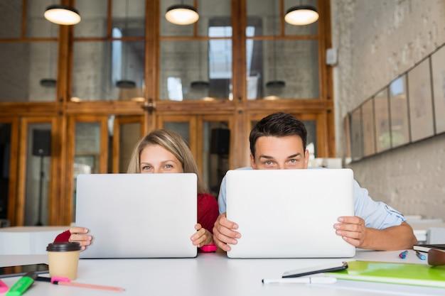 Молодой мужчина и женщина, работающая на ноутбуке в коворкинг-офисе открытого пространства,