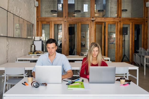 Молодой мужчина и женщина, работающая на ноутбуке в коворкинг-офисной комнате открытого пространства