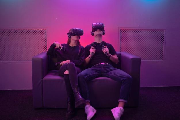 Молодой человек и молодая женщина, сидя на диване и играя в игры.