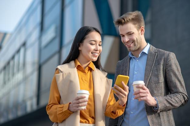 スマートフォンで写真を見ながら笑っている若い男性と若い女性