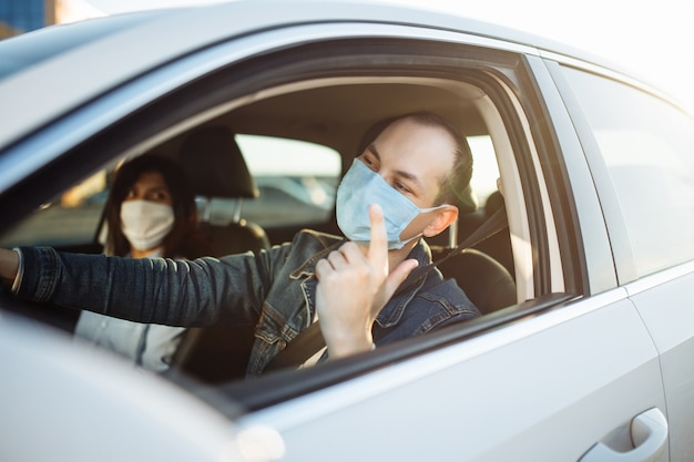 Young man angry drives a car with a passenger during coronavirus pandemic.