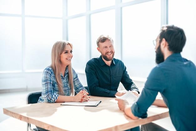 Молодой человек отвечает на вопросы интервьюеров в офисе. концепция сотрудничества