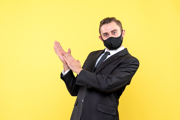 黄色で誰かを拍手する若い男