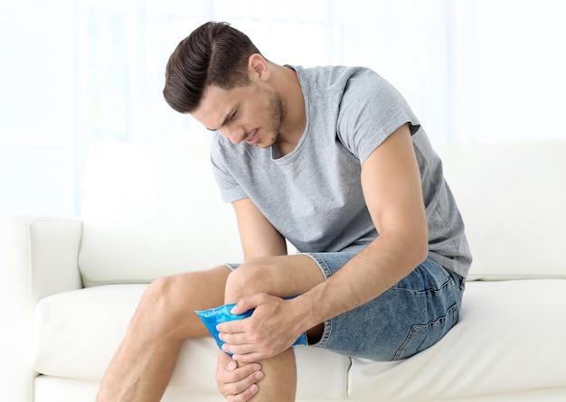 自宅で脚に冷湿布を適用する若い男