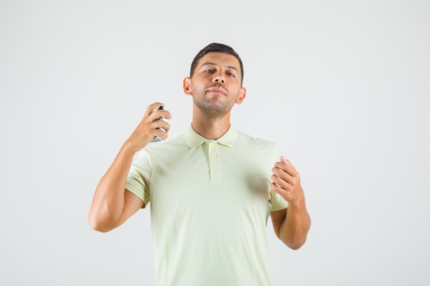 Young man applying perfume on his neck in t-shirt front view.