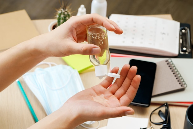 若い男がオフィスで彼の作業テーブルに座っている間彼の手に消毒ゲルを適用します