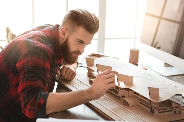 オフィスの職業で働く若い男の建築家