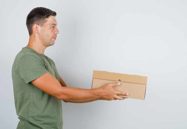 Young man in army green t-shirt delivering cardboard box .