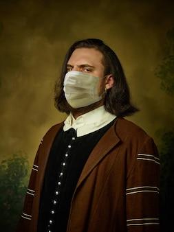 코로나바이러스에 대한 보호 마스크를 쓰고 어두운 배경에 중세 기사로 젊은 남자