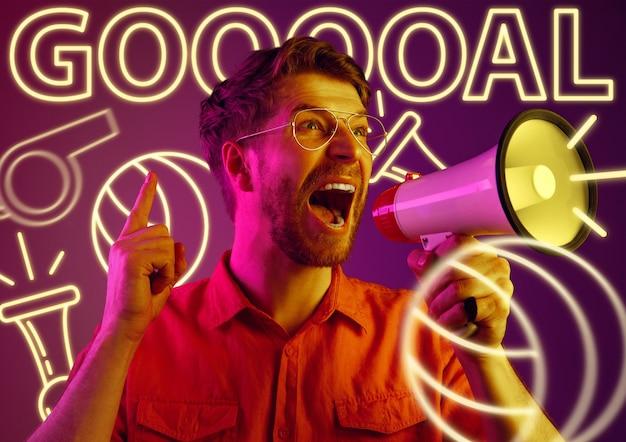 Молодой человек как фанат спорта на фиолетовом фоне в неоновом свете. мужская модель кричит, болеет за любимую футбольную или футбольную команду. концепция выражения лица, лето, отдых, спорт, ставки.