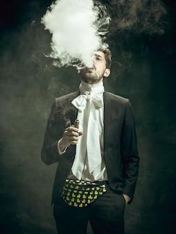 어두운 배경에 도리안 그레이로 젊은 남자. 레트로 스타일, 시대 개념의 비교.