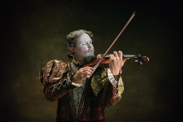 짙은 녹색 배경에 고립 된 요한 바흐로 젊은 남자. 복고 스타일, 시대 개념의 비교입니다. 역사적 인물, 위대한 음악 작곡가, 구식 같은 아름다운 남성 모델.