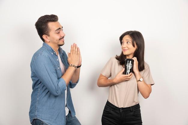 젊은 여자에서 커피 한 잔을 요구하는 젊은 남자.