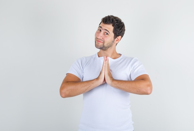 Young man asking for forgiveness while smiling in white t-shirt and looking hopeful