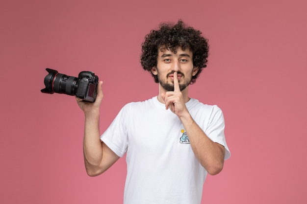 Young man asking to keep silent and holding photocamera