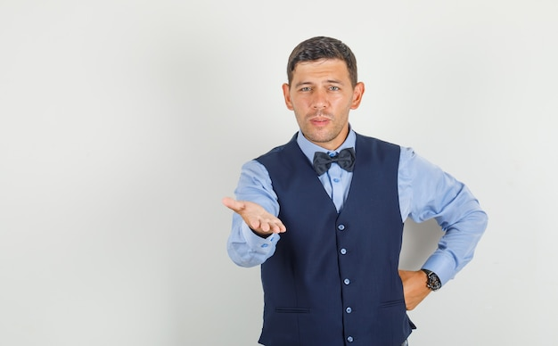 Young man asking question with hand on waist in suit