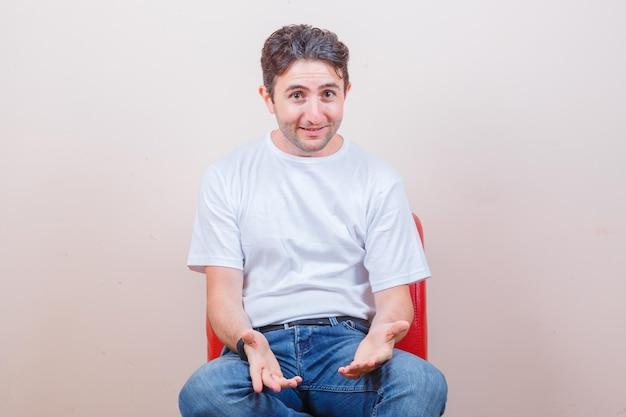 Tシャツ、ジーンズ、陽気に椅子に座って何かを尋ねる若い男